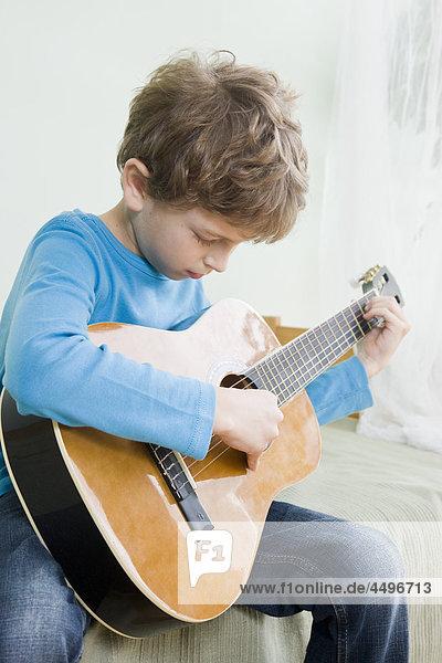 Junge spielt auf Gitarre