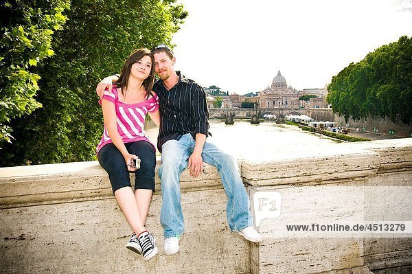 Portrait of young couple sitting on ledge with Saint Peter's Basilica behind  Rome  Italy