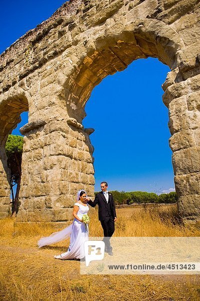 Bride and groom walking together in under ancient aqueduct roman ruins in Rome Italy
