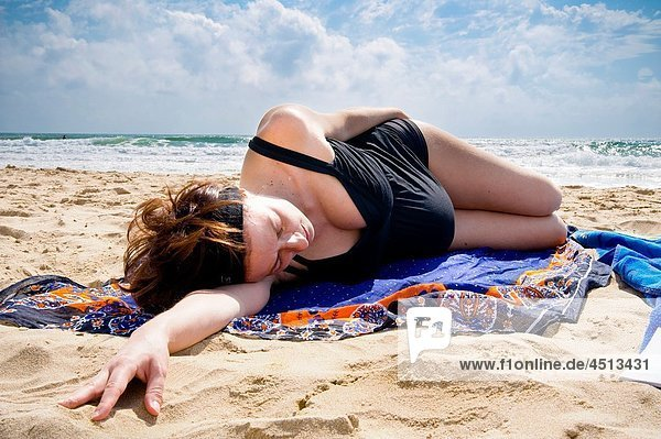 Pregnant woman laying down on the beach by the sea