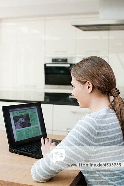 Junge Frau betrachtet Haustierversicherung auf Laptop