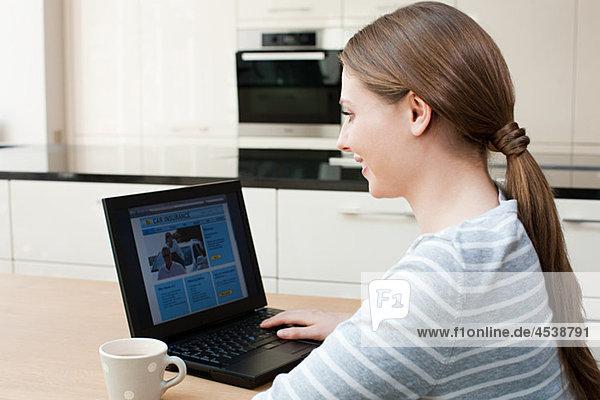 Junge Frau betrachtet Autoversicherung auf Laptop