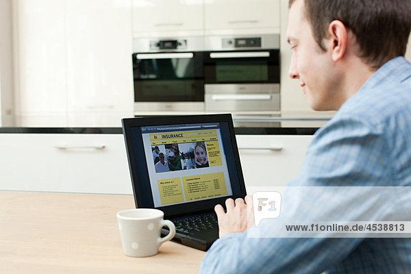 Junger Mann sucht Versicherung am Laptop