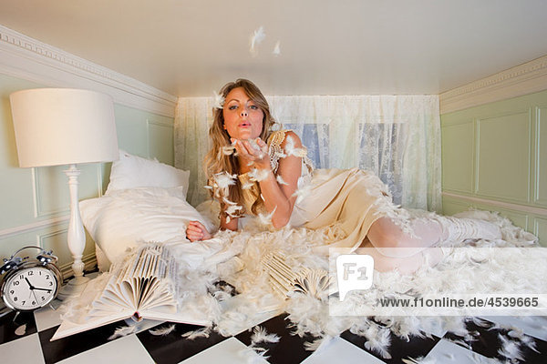 Junge Frau in kleinem Raum,  blasende Kissenfedern
