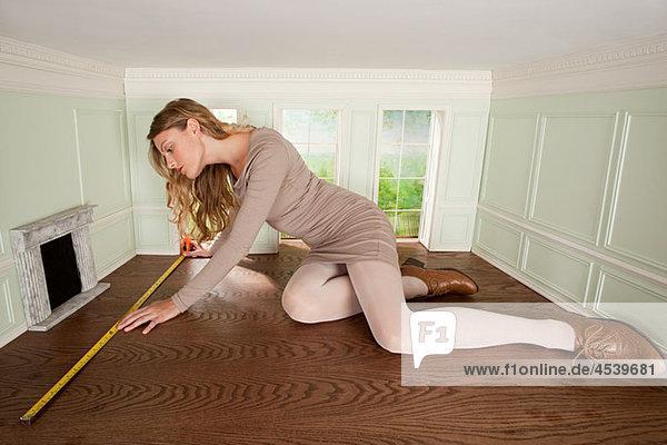 Junge Frau in kleinem Raum mit Bodenmessung
