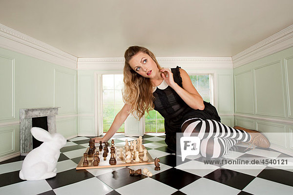 Junge Frau beim Schachspiel mit Kaninchen