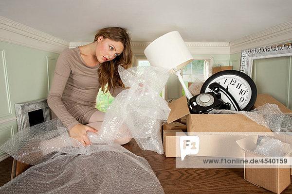 Junge Frau beim Packen von Gegenständen in einem kleinen Raum