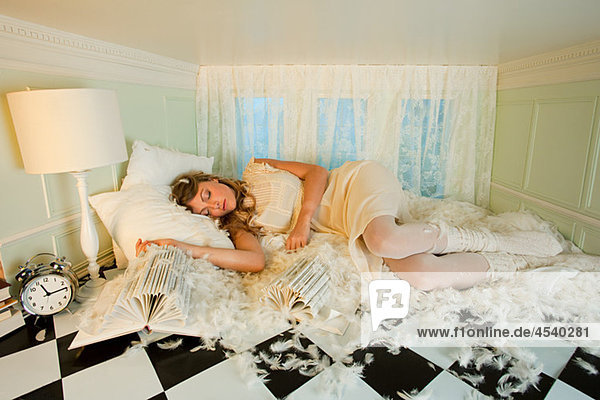 Junge Frau schläft zwischen Kissenfedern im kleinen Zimmer