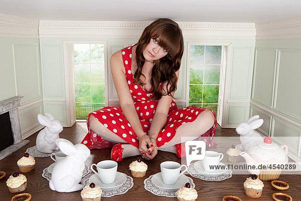 Junge Frau bei einer Teeparty in einem kleinen Raum