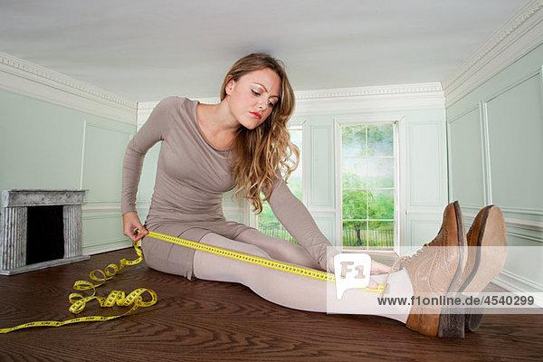 Junge Frau in kleinem Raum  die ihr Bein misst