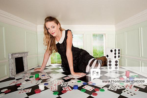 Junge Frau im kleinen Zimmer mit Spielkarten und Würfeln