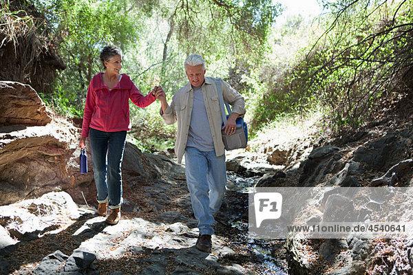 Ein reifes Paar  das im Wald spazieren geht.