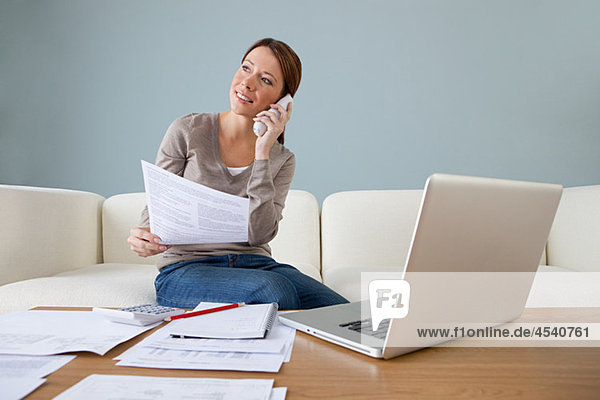 Junge Frau am Telefon mit Laptop