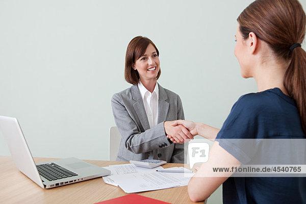 Junge Frau beim Händeschütteln mit Finanzberaterin