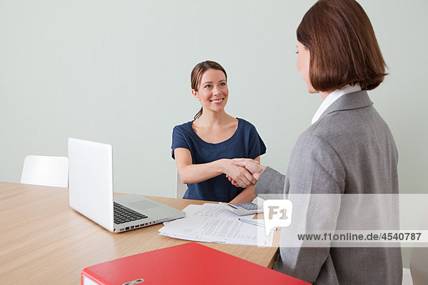 Young woman shaking hands with financial adviser