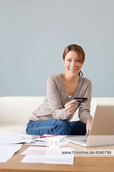 Young woman with credit card using laptop