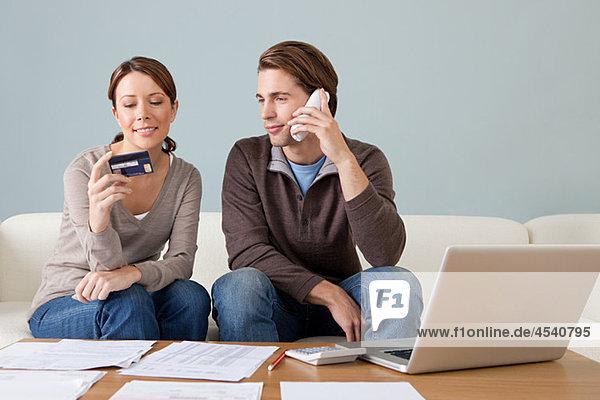 Junges Paar mit Computer und Papierkram