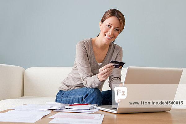 Junge Frau mit Kreditkarte mit Laptop