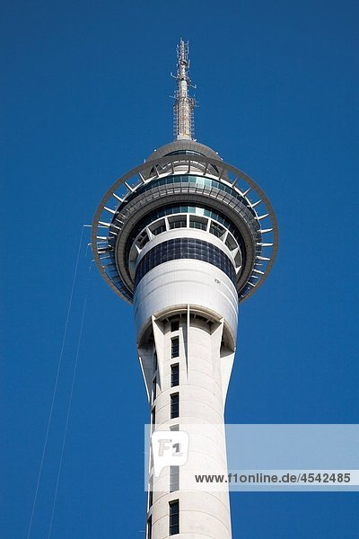 Auckland North Island New Zealand Sky Tower observation and radio tower upper section with restaurant levels and two observation decks in city centre against blue sky