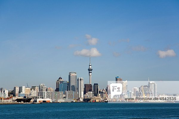 Auckland North Island New Zealand Central Business District skyline Sky Tower and international container ports on eastern waterfront from across Waitemata Harbour