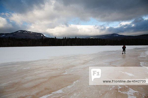 Hiker snowshoeing on the edge of Church Pond in the White Mountains  New Hampshire USA This area was part of the Swift River Railroad era  which was an logging railroad in operation from 1906 - 1916