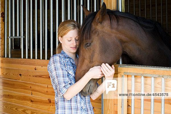 Mittlere erwachsene Frau mit Pferd im Stall