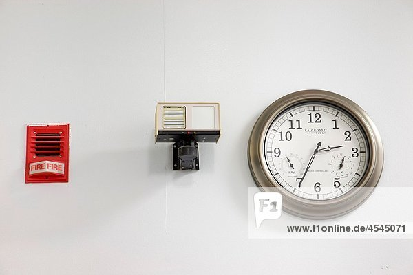 Fire alarm  sensor  and clock on a business office wall