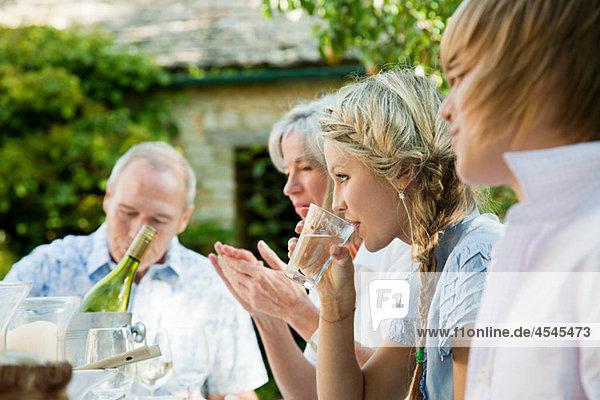 Junge Frau trinkt Wasser mit Familie