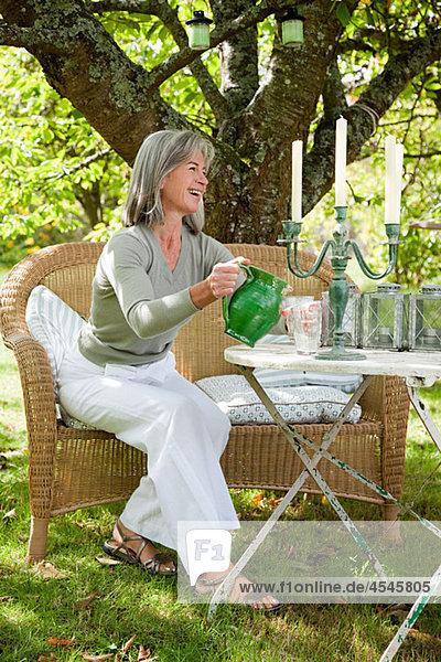 Reife Frau Gießen Wasser aus Krug