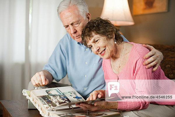 Seniorenpaar schaut sich Familienalbum an