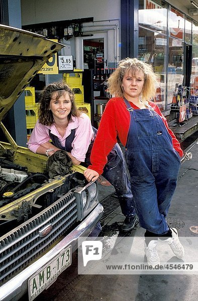 two female mechanics outside their workshop posing for the camera