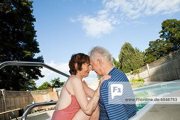 Loving senior couple by swimming pool