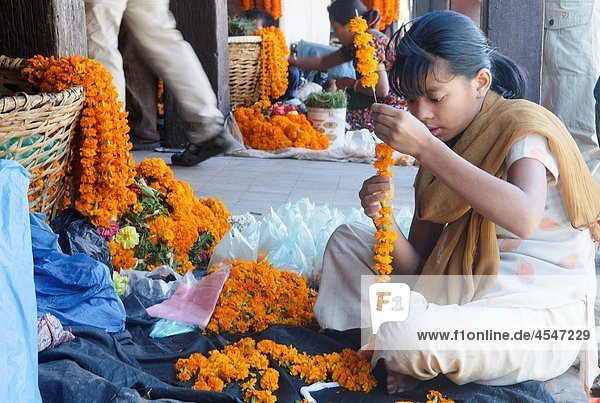girl making garlands of marigolds at a temple in Durbar Square in Kathmandu  Nepal