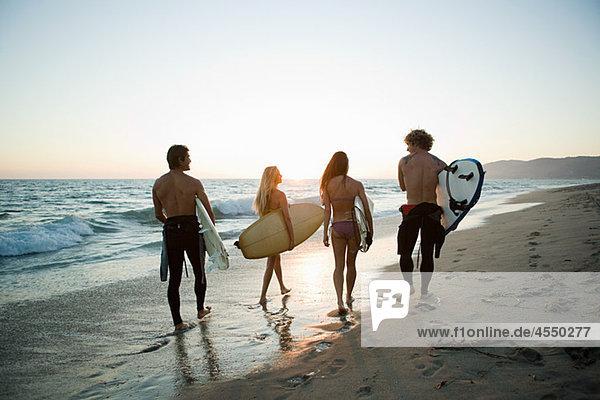 Rückansicht der Surfer am Strand bei Sonnenuntergang