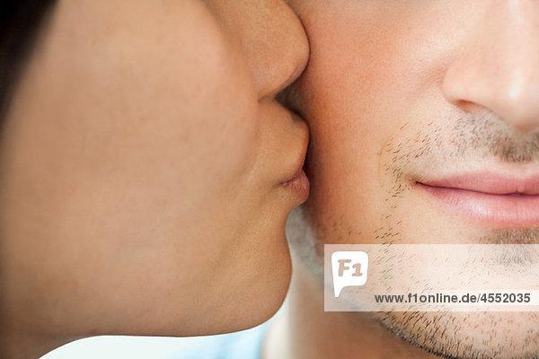 Frau küsst den Mann auf die Wange  den Mund.