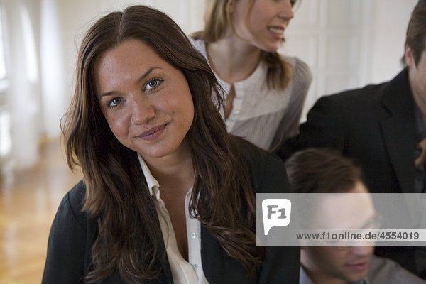 Porträt der jungen geschäftsfrau mit Kollegen im Hintergrund Porträt der jungen geschäftsfrau mit Kollegen im Hintergrund