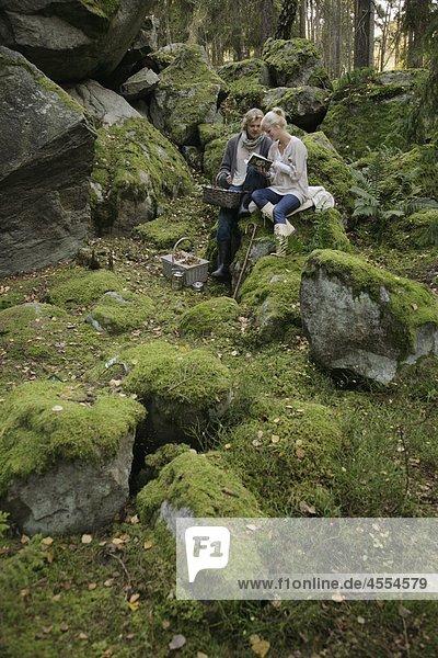 junges Paar auf Moosbedeckte Rock sitzen  lesen und halten Picknick-Korb