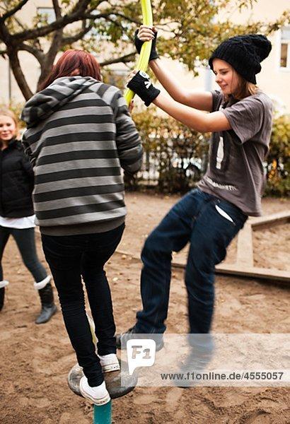 Jugendliche spielen auf Klettergerüst im Schulhof