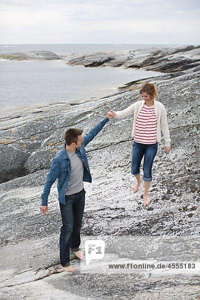 Mitte adult paar Wandern am Strand und Hände