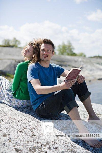 Mitte adult paar am Strand sitzen und wegsehen  Mann  Buch hält