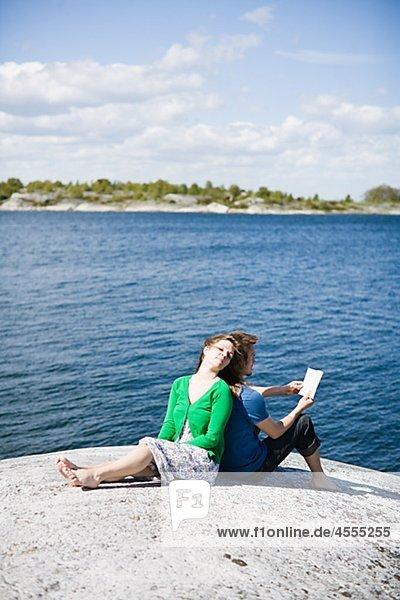 Mitte adult paar am Strand sitzen und wegsehen  Mann Buch zu lesen