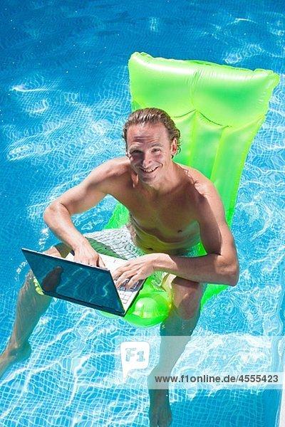 sitzend Mann Notebook arbeiten aufblasen Floß