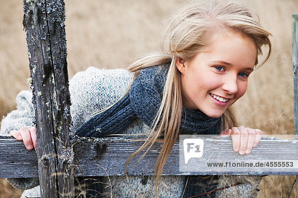 Portrait of teenage girl wearing scarf in field