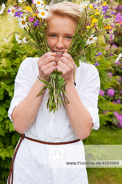 Portrait of teenage girl with bunch of flowers