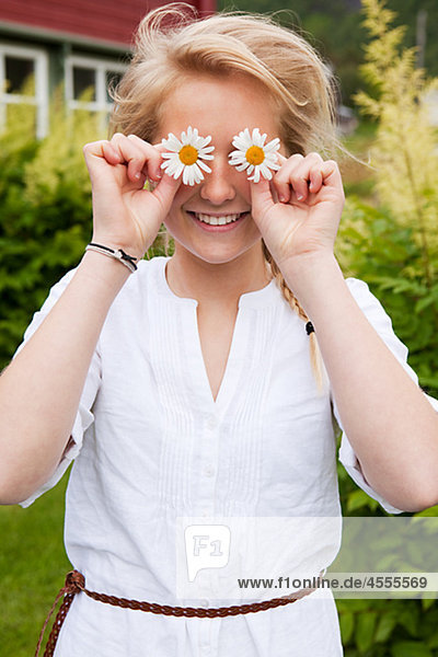 Portrait of teenage girl holding flowers over eyes