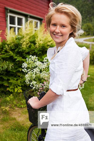 Portrait of teenage girl with bicycle