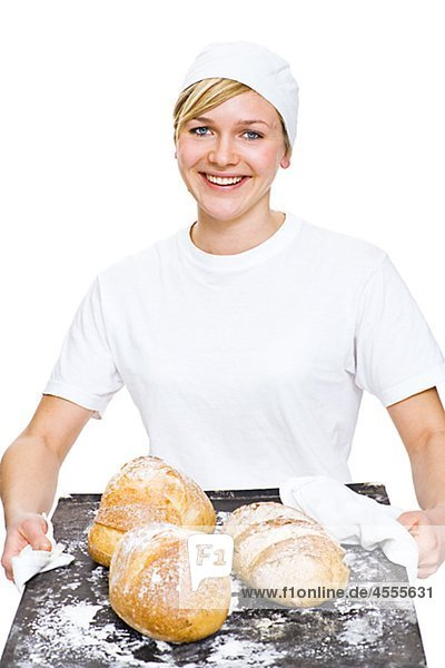 Frau hält Backblech mit Brot  Lächeln  portrait