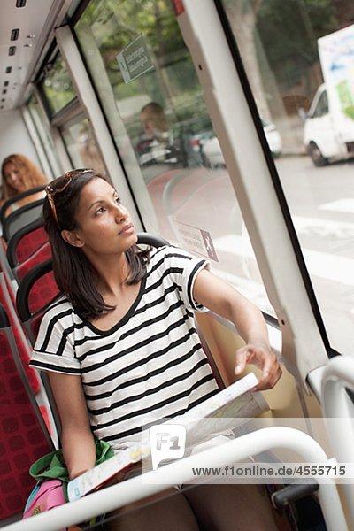Frau mit Karte durch Bus Fenster Suchen