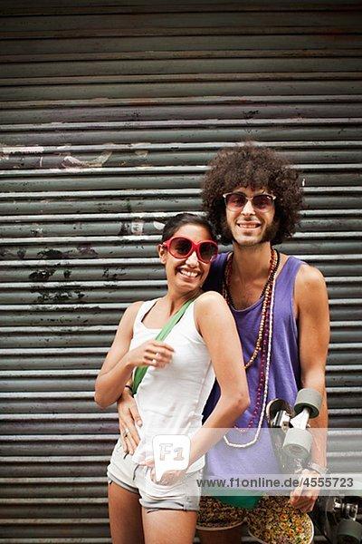 Porträt jungen Paares von Garagentor umarmen
