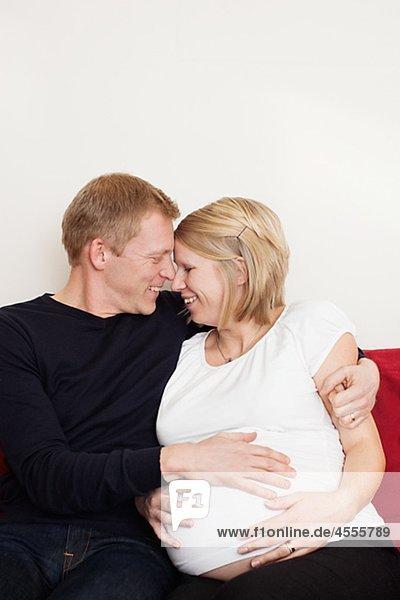 Mann mit schwangere Frau sitzt auf Sofa und suchen einander